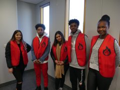 Students from future Social Services Institute wearing the bright red volunteer vests.